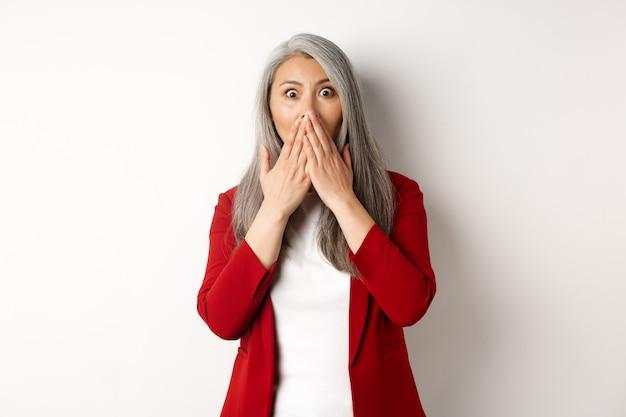 Scioccata signora asiatica senior ansimante, coprire la bocca dallo stupore, sentire i pettegolezzi, in piedi su sfondo bianco.