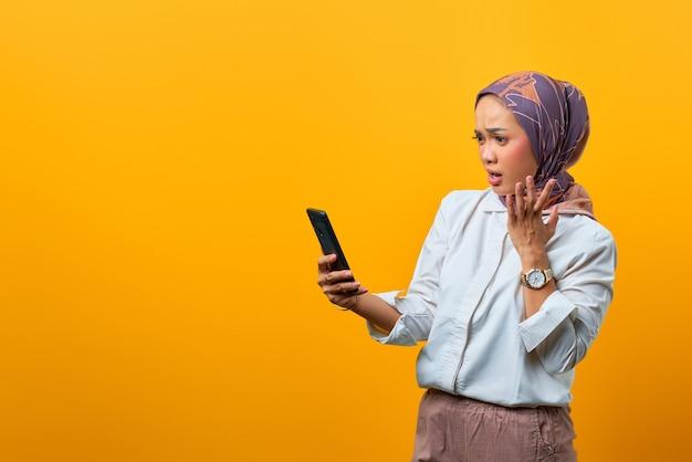 Donna asiatica scioccata che guarda lo smartphone con la bocca aperta e la mano alzata su sfondo giallo
