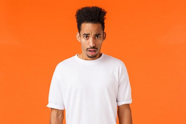 Giovane maschio afroamericano scioccato e sbalordito, senza parole con baffi, acconciatura afro, rabbia da disgusto, scena terribile, bocca aperta senza fiato confusa e frustrata, arancione
