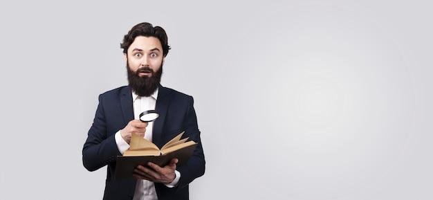 Uomo barbuto scioccato che legge il libro con lente d'ingrandimento, maschio sopra il muro grigio, mock-up panoramico con spazio per il testo