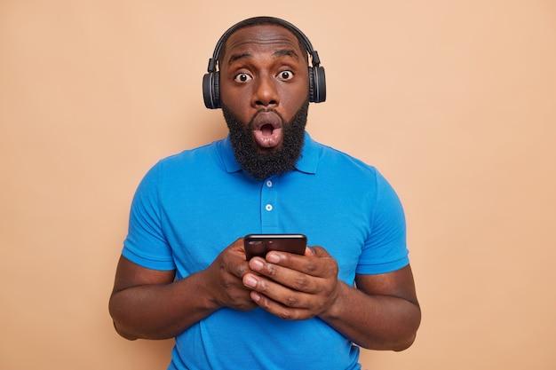 L'uomo barbuto scioccato con tiene un gadget moderno ascolta musica tramite le cuffie scarica una nuova canzone nella playlist tiene la bocca aperta isolata sul muro marrone