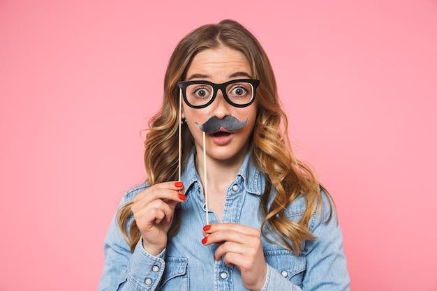 Donna bionda scioccata che indossa una camicia di jeans in posa con baffi finti e occhiali mentre guarda la parte anteriore sul muro rosa