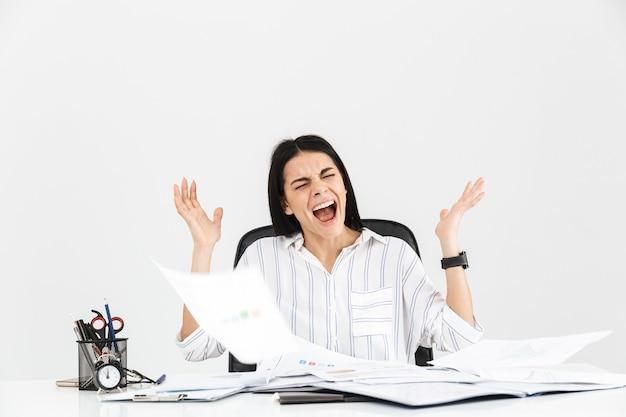 Imprenditrice bruna scioccata urlando e sottolineando mentre si lavora con documenti cartacei in ufficio isolato sopra il muro bianco