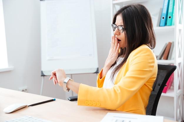 Donna d'affari scioccata che guarda l'orologio da polso in ufficio