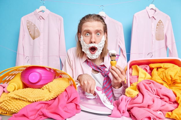 Il marito di casa scioccato e impegnato fa diversi compiti contemporaneamente stira il bucato si fa la barba in ritardo per il lavoro si veste velocemente fa i lavori di casa fissa gli occhi spiaccicati