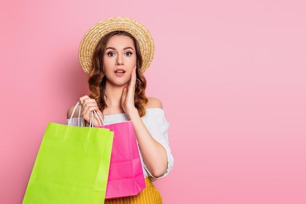 La ragazza caucasica colpita in un cappello di paglia e un vestito bianco tiene i sacchetti della spesa in mani isolate su una parete rosa. la ragazza emozionante sorpresa fa il concetto online di vendita dell'insegna di web di acquisto