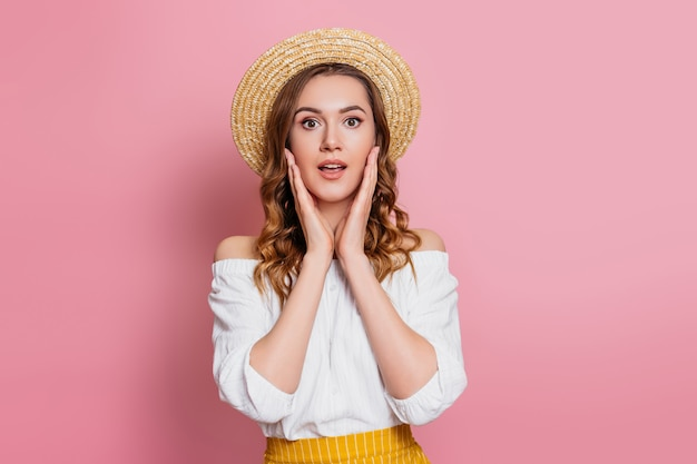 Ragazza caucasica colpita in un cappello di paglia e vestito bianco d'annata isolati su una parete rosa. concetto emozionante sorpreso di vendita dell'insegna di web della ragazza