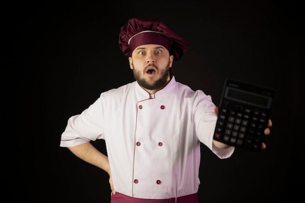 L'uomo scioccato del cuoco unico in uniforme tiene la calcolatrice nel panico esamina la macchina fotografica