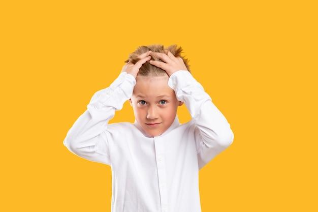 Ritratto di bambino scioccato. attacco di panico. ragazzo sopraffatto in camicia bianca che stringe la testa isolata sull'arancia.