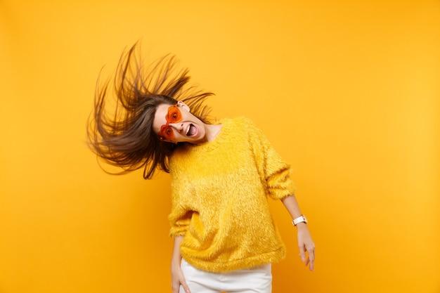 Ragazza comica scioccata in maglione di pelliccia, occhiali arancioni a cuore che scherzano in studio, saltando con i capelli spazzati dal vento isolati su sfondo giallo. persone sincere emozioni stile di vita. zona pubblicità.