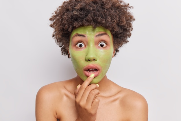 La donna dai capelli ricci scioccata applica una maschera nutriente di avovado sul viso e fa procedure di ringiovanimento