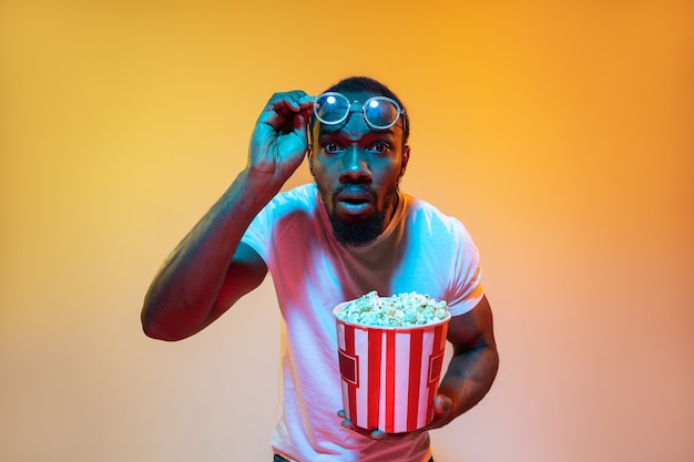 Scioccato, incredulo. ritratto moderno dell'uomo afroamericano su sfondo arancione sfumato in luce al neon. bellissima modella afro. concetto di emozioni, cinema, espressione facciale, vendite, pubblicità.