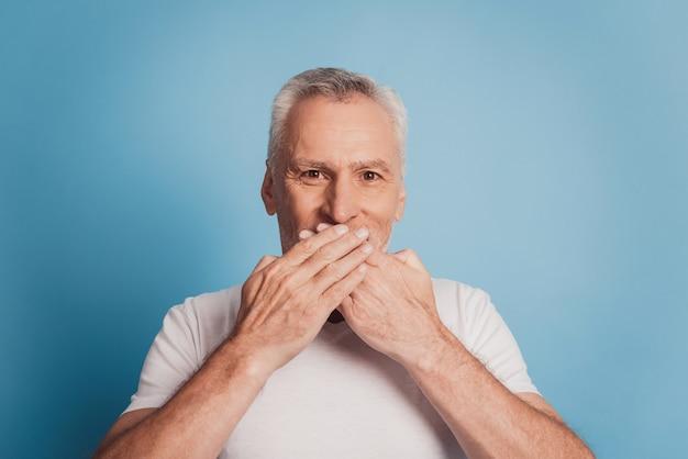 Scioccato anziano uomo dai capelli grigi coprire la bocca con le mani isolate su sfondo blu studio