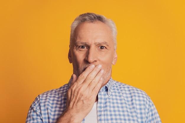 Scioccato anziano uomo dai capelli grigi coprire la bocca con le mani isolate su sfondo giallo studio