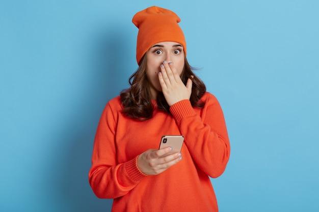 Donna scioccata con il telefono in mano ascoltando notizie sorprendenti, ha un'espressione spaventata, coprendo la bocca con il palmo, guarda la telecamera con grandi occhi, isolata sopra la parete blu.