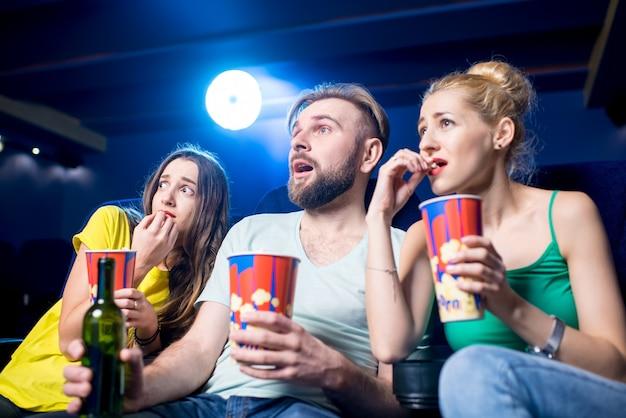 Amici scioccati che guardano film seduti insieme a popcorn al cinema