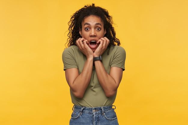 Una giovane donna spaventata e scioccata in abiti casual tiene le mani sulle guance e sembra impaurita isolata sul muro giallo