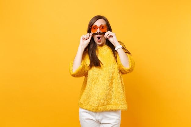 Scioccata e divertente giovane donna in maglione, pantaloni bianchi, occhiali arancioni a cuore che tengono i capelli come baffi isolati su sfondo giallo brillante. persone sincere emozioni, concetto di stile di vita. zona pubblicità.