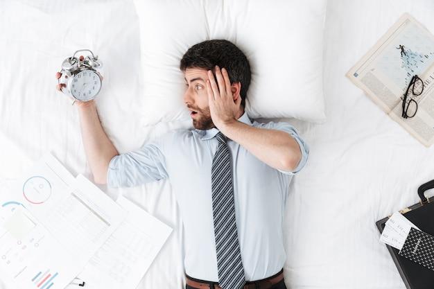 Scioccato bel giovane uomo d'affari al mattino a letto giace addormentato tenendo sveglia
