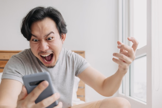 L'uomo scioccato e felice riceve buone notizie dallo smartphone