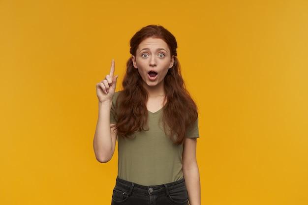 Ragazza dall'aspetto scioccato, donna rossa eccitata con i capelli lunghi. indossare una maglietta verde. concetto di persone ed emozione. alza il dito, ho un'idea. isolato sopra il muro arancione