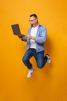 Uomo scioccato che salta isolato sopra la parete gialla utilizzando il computer portatile.
