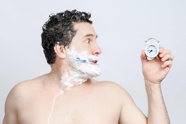 Scioccato uomo bianco di mezza età con spazzolino da denti in bocca, rasatura, lavaggio della testa, guarda di profilo sulla sveglia in mano e fretta, essendo in ritardo al lavoro o una riunione, dormito troppo su sfondo bianco