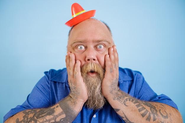 L'uomo obeso scioccato con un piccolo sombrero tiene le guance su sfondo azzurro