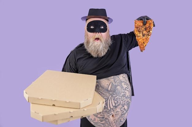 L'uomo grassoccio scioccato in costume da eroe tiene scatole e una fetta di pizza su sfondo viola