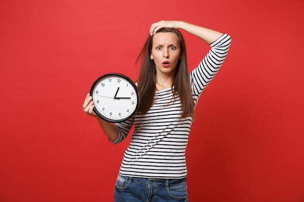 Scioccato perplesso giovane donna in abiti a righe mettendo la mano sulla testa tenendo l'orologio rotondo isolato su sfondo rosso. il tempo sta finendo. persone sincere emozioni, concetto di stile di vita. mock up copia spazio.