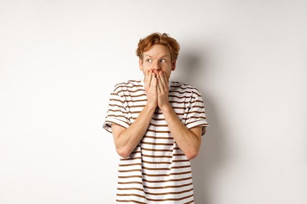 Ragazzo dai capelli rossi scioccato spettegolare, ridacchiare in mano e guardando lasciato impressionato, in piedi su sfondo bianco.