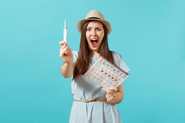 Donna triste scioccata in abito blu, cappello tenere in mano test di gravidanza, calendario dei periodi per controllare i giorni delle mestruazioni isolati su sfondo blu. concetto medico, sanitario, ginecologico. copia spazio.