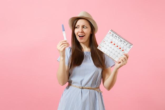 Donna triste scioccata in abito blu, cappello tenere in mano test di gravidanza, calendario dei periodi per il controllo dei giorni delle mestruazioni isolati su sfondo rosa. concetto medico, sanitario, ginecologico. copia spazio.