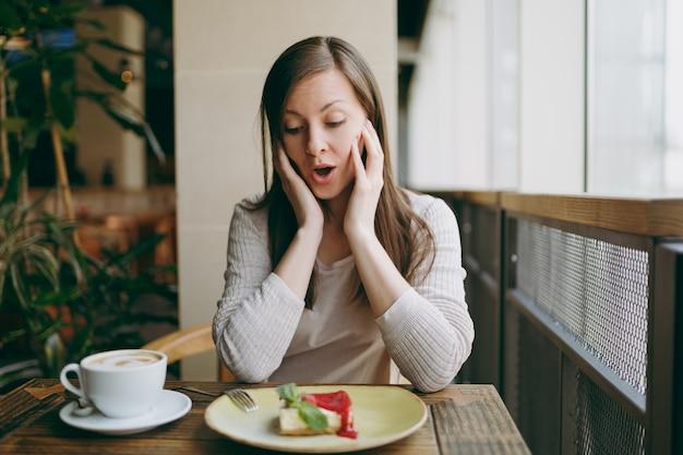 Scioccato triste giovane donna seduta da sola vicino alla grande finestra nella caffetteria al tavolo con una tazza di cappuccino, torta, rilassante nel ristorante durante il tempo libero. giovane femmina che ha resto in caffè. concetto di stile di vita