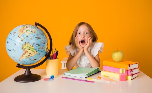 Una studentessa scioccata in uniforme è seduta a un tavolo con materiale scolastico su uno sfondo giallo con una copia dello spazio. di nuovo a scuola