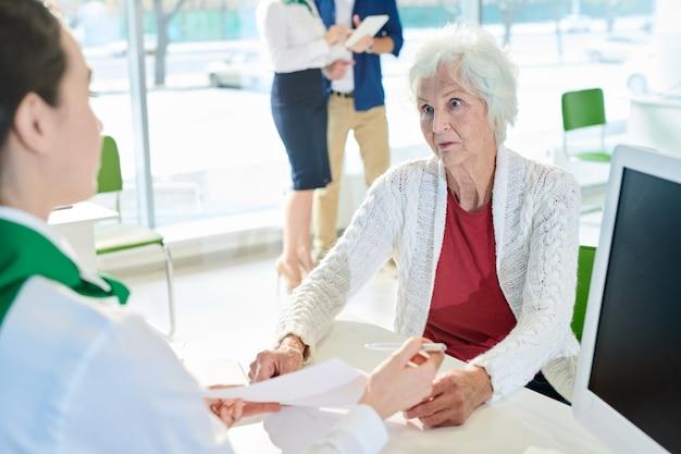 Cliente senior colpito che esamina lo specialista della banca