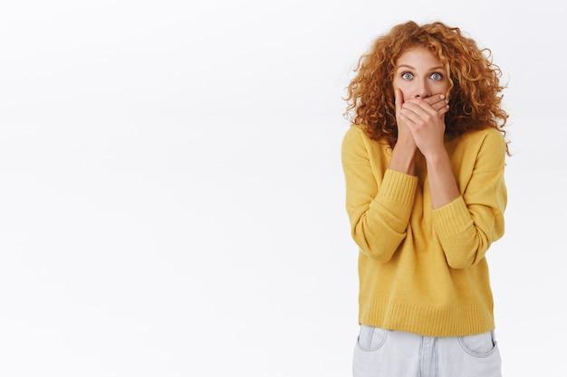 Scioccata, senza parole, attraente donna riccia rossa in maglione giallo, ansimando, chiudendo la bocca, premendo le mani sulle labbra, fissa stupita, ascolta voci incredibili, spettegola, resta sorpresa