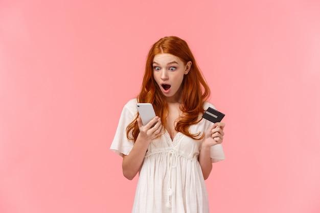 Giovane ragazza caucasica rossa scioccata e sorpresa che vede qualcosa tremare sul suo conto bancario tramite l'app per smartphone, con cellulare e carta di credito, guarda il display con la mascella caduta