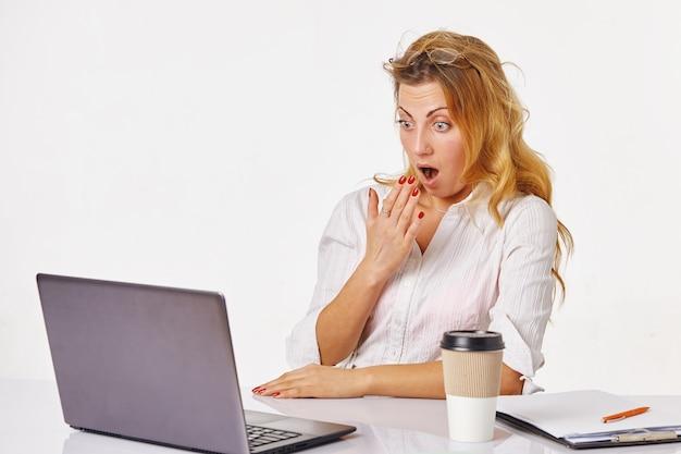 Uomo d'affari scioccato e sorpreso che si siede davanti al computer portatile