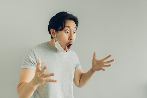 Volto scioccato e sorpreso dell'uomo che indossa una maschera igienica bianca in maglietta grigia.