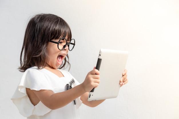 Bambina scioccata e sorpresa su internet con il concetto di computer tablet digitale per stupore, stupore, commettere un errore, stordito e senza parole o vedere qualcosa che non dovrebbe vedere