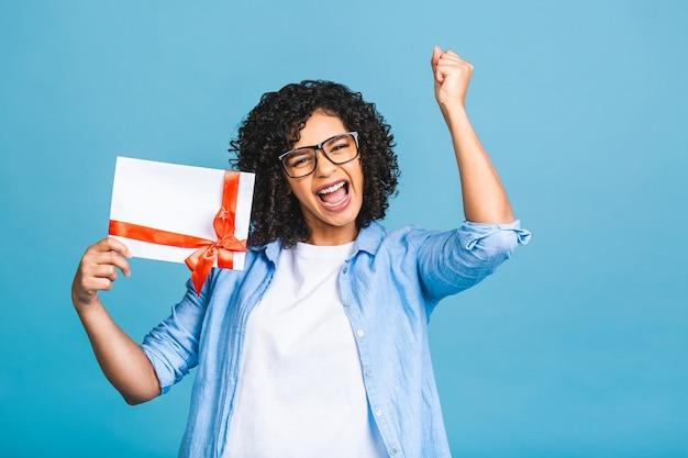 Giovane donna afroamericana riccia sorpresa scioccata isolata sul ritratto blu dello studio del fondo. mock up copia spazio. tenendo il buono regalo.
