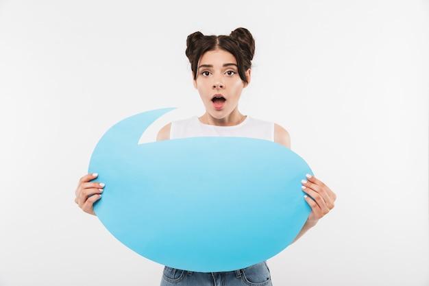 Giovane donna scioccata o sorpresa con l'acconciatura dei doppi panini che tiene insegna pubblicitaria vuota per il testo del copyspace, isolata su bianco