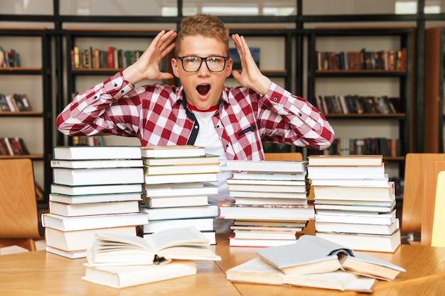 Ragazzo adolescente scioccato seduto al tavolo della biblioteca