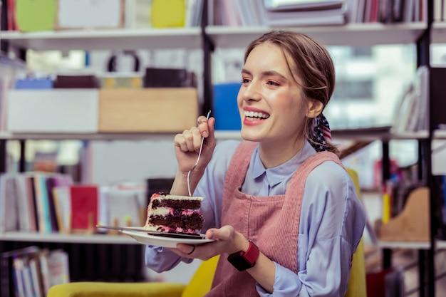Scioccato dal gusto. ragazza attraente di risata che separa il pezzo di torta con la forchetta e desiderando un morso