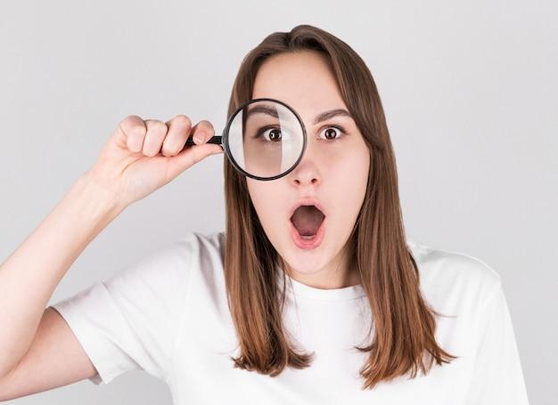 Donna scossa che osserva tramite una lente d'ingrandimento