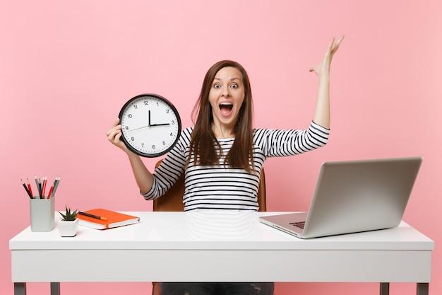 Donna scioccata che urla allargando le mani tenendo la sveglia seduta, lavora in ufficio con un computer portatile isolato su sfondo rosa pastello. concetto di carriera aziendale di successo. copia spazio. il tempo sta finendo.