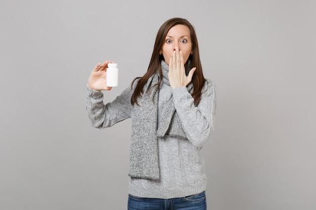 Donna scioccata in maglione, sciarpa che copre la bocca con compresse di farmaci da tenere in mano pillole di aspirina in bottiglia isolato su sfondo grigio. trattamento di malattia malato malato di stile di vita sano, concetto di stagione fredda.