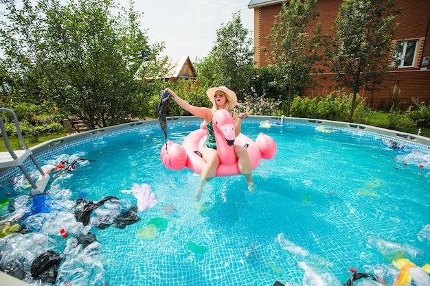 Donna scioccata nuota in una piscina inquinata. bottiglie e sacchetti di plastica galleggiano vicino a lei.