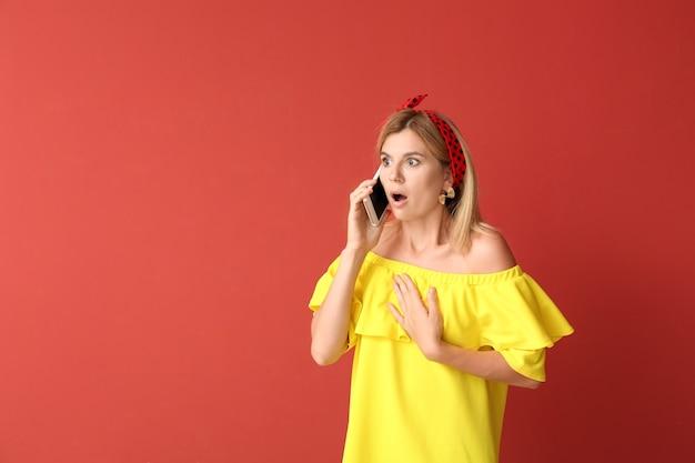 Donna scioccata che parla al cellulare